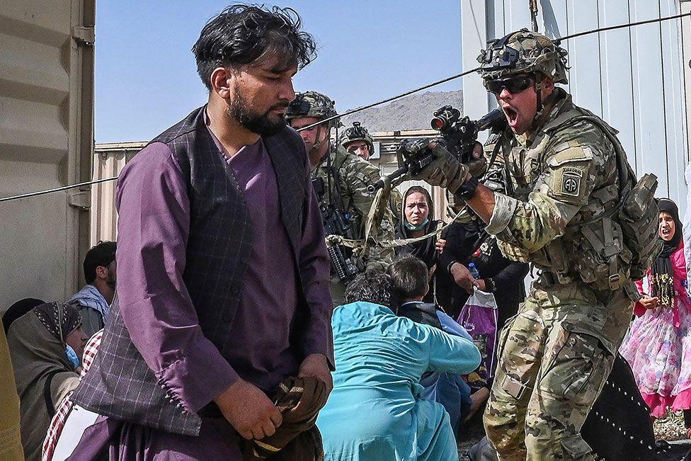 Ένας Αμερικανός στρατιώτης δείχνει το όπλο του προς έναν Αφγανό επιβάτη στο αεροδρόμιο της Καμπούλ στην Καμπούλ στις 16 Αυγούστου 2021